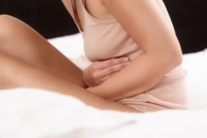 Frau mit akuten Bauchschmerzen im Bett
